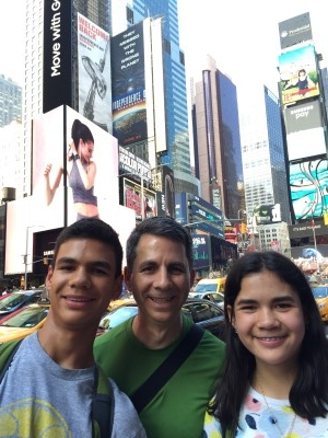David and the kids hemmed in by Times Square, people, and a sea of taxis behind them.