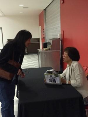 Signing a book for Joy, a good friend of my cousin Debi (courtesy of Debi Ecobiza).