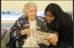 Rasheeda Ramsingh reading a holiday card with a woman in a senior home.  Photo Credit: Fawzia Rahman