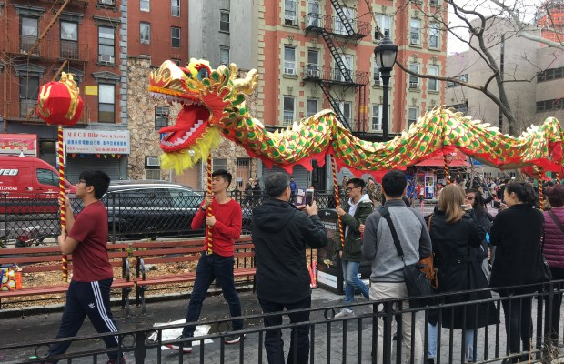 Caption for dragon: Performers carry a dragon through the crowd on poles to spread good luck in a traditional dragon dance. Photo Credit: Marilyn Ramos