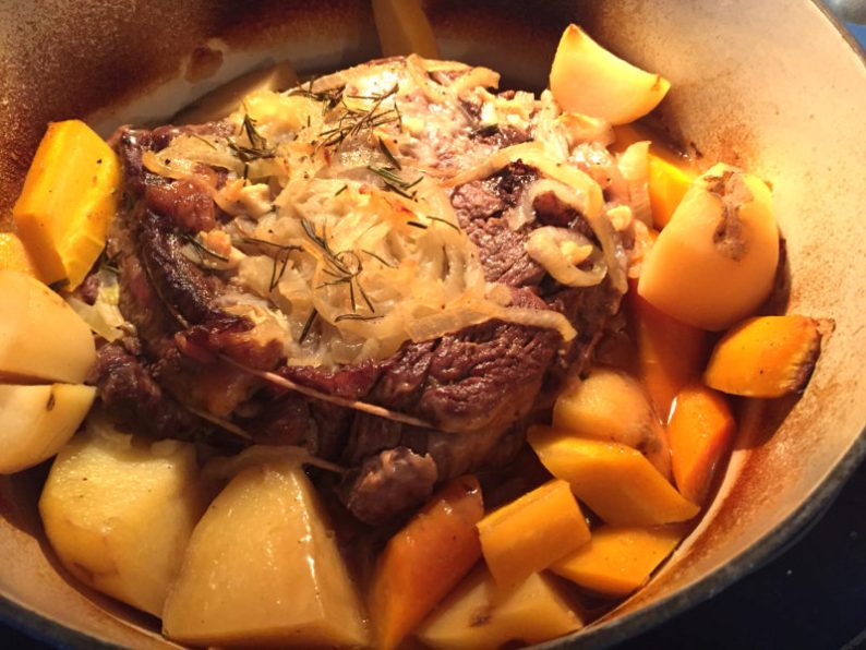 A chuck roast is braised in a Dutch oven with onions and surrounding vegetables of potatoes and carrots