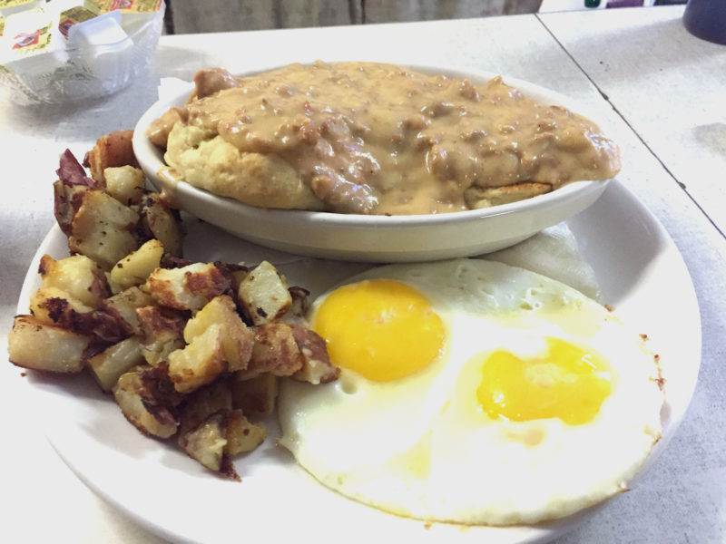 Sausage gravy over biscuits with eggs and homefries