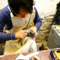 Yusuke preparing to hand stitch a sole.
