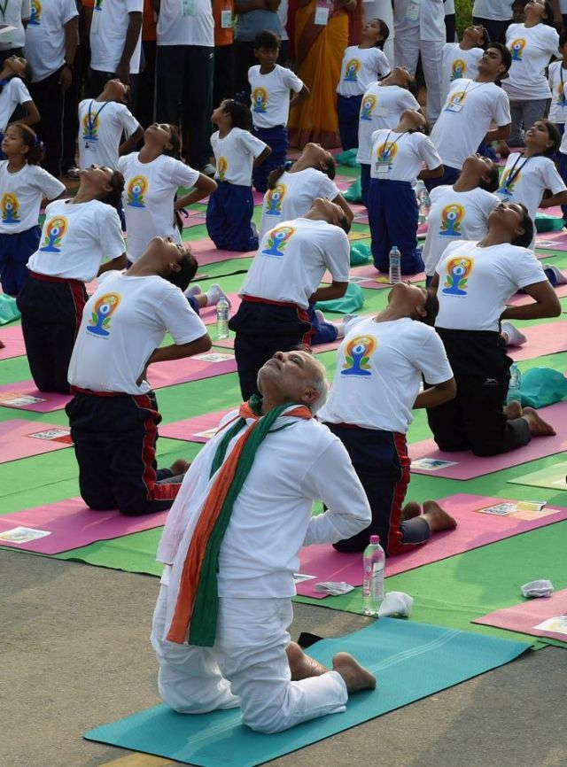 New Delhi: Prime Minister Narendra Modi performs yoga along with thousands of others at a mass yoga session to mark the International Day of Yoga 2015 at Rajpath in New Delhi on Sunday. PTI Photo by Atul Yadav(PTI6_21_2015_000014B)