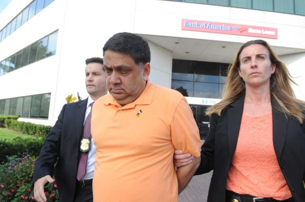 Harendra Singh is led out of the FBI office in Melville early Wednesday, Sept. 9, 2015.