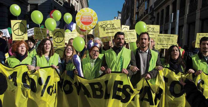 Greenpeace activists, demanding 100% renewable energy at Climate March 2015 in Madrid.
