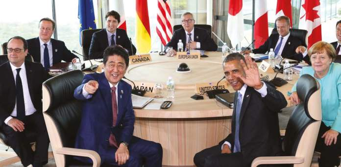 Japanese Prime Minsiter Shinzo Abe, foreground center left, and U.S. President Barack Obama, foreground center right, smile at photographers with other leaders of Group of Seven industrial nations, clockwise from left, French President Francois Hollande, British Prime Minister David Cameron, Canadian Prime Minister Justin Trudeau, European Commission President Jean-Claude Juncker, European Council President Donald Tusk, Italian Prime Minister Matteo Renzi and German Chancellor Angela Merkel, at the start of the second working session of the G-7 summit meetings in Shima, Mie Prefecture, Japan, Thursday, on May 26, 2016. (AP)