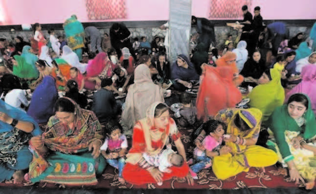 Hindu and Sikh families wait for lunch inside a Gurudwara in Kabul