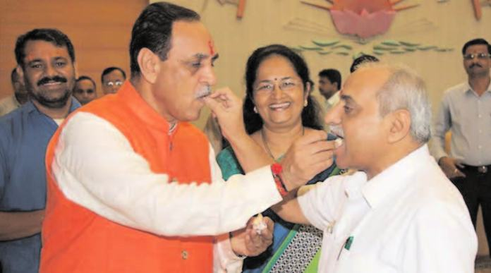 Gujarat Chief Minister Vijay Rupani and Deputy Chief Minister Nitin Patel share sweets at CMO before taking charge as the Gujarat Chief Minister at Gandhinagar on Monday. - Image - PTI