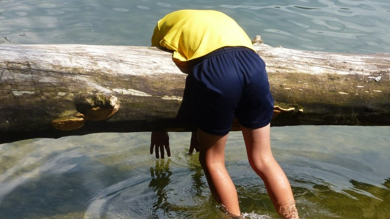 Tired person hanging over a log