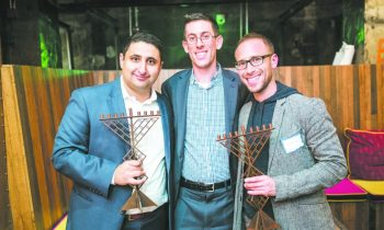 Vadim Avshalumov of Detroit, Adam Finkel of Bloomfield Hills and Perry Teicher of New York, organizers of a reception for Jew-ish expats, with chanukiot created by Erik and Israel Nordin