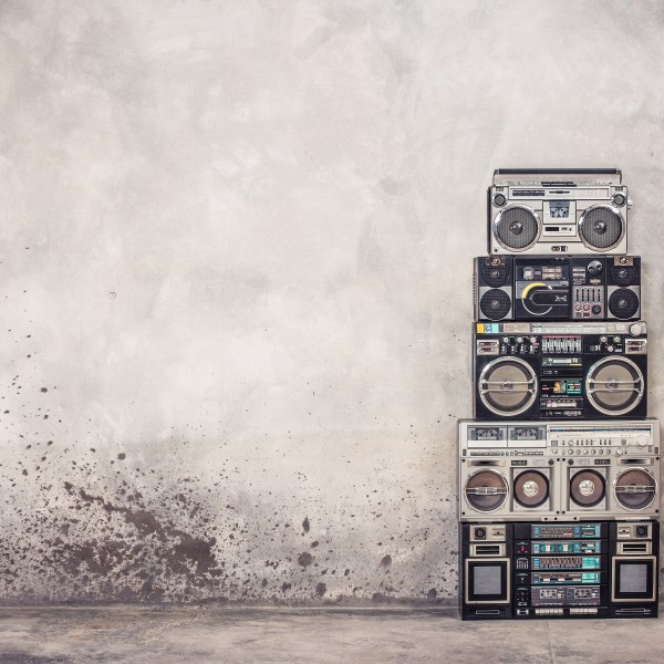 Retro old school design ghetto blaster boombox stereo radio cassette tape recorders tower from circa 1980s front concrete wall background. Vintage style filtered photo