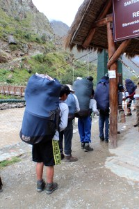 The line-up of porters waiting to go through the control booth with their backpacks full of  25kg of gear.