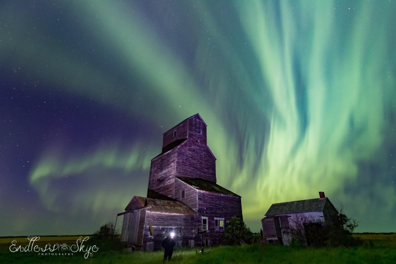 Bands of green northern lights flaring out behind an old grain elevator lit up by another photographer in the photo.