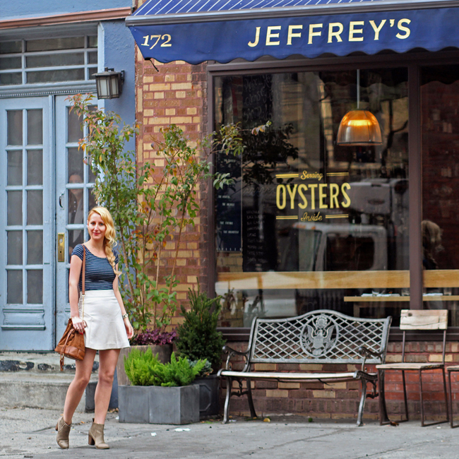 Fall in the West Village wearing a blue striped top, beige skirt, taupe ankle boots, and brown bucket bag
