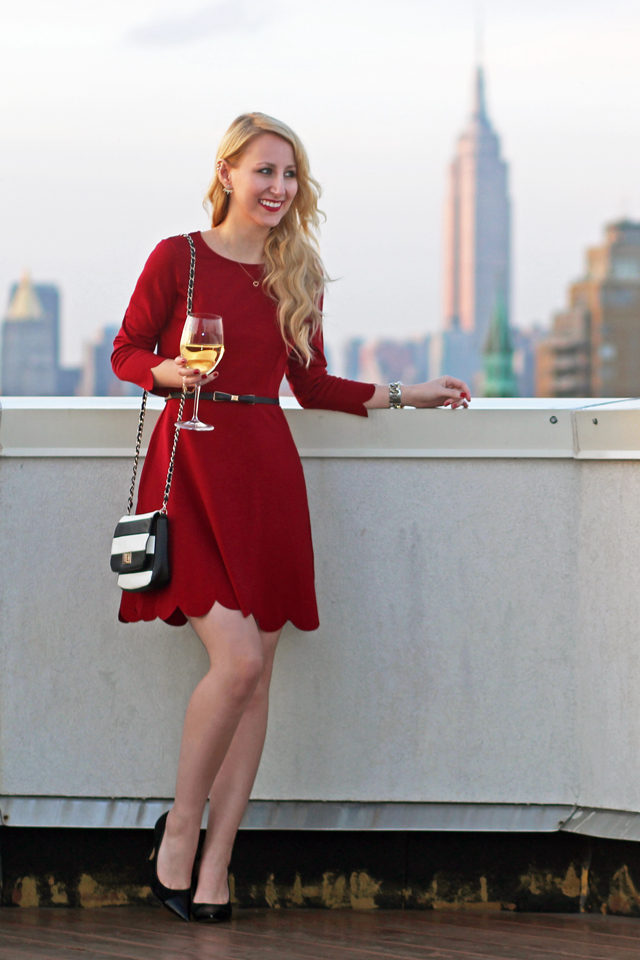 red holiday dress with black pumps and striped bag
