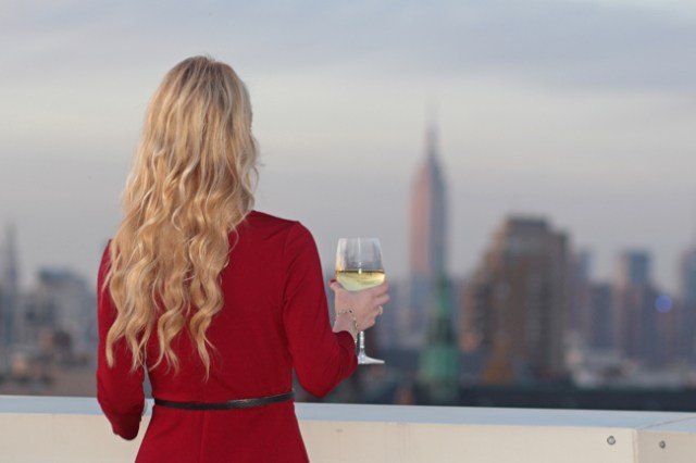 Wearing a red dress with a view of New York City skyline