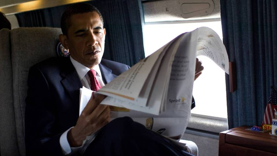 President Barack Obama reads a morning newspaper aboard Marine One while en route to the US Naval Academy commencement, May 22, 2009