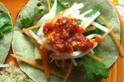 Banh mi tacos: layered chicken, cilantro, pickled carrot and jicama, and sriracha, on a tortilla.