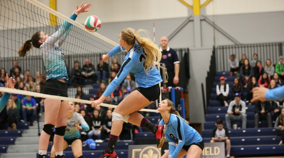 Mid Natalie Crews goes in for a spike. Photo by Northfield Photography.