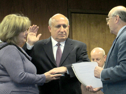 Photo by Ron LeirPeter Norcia (c.) is sworn in as North Arlington councilman by Mayor Peter Massa as Norcia's wife Pat holds Bible.