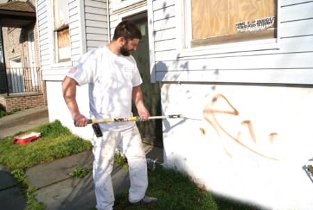 Photos by Karen Zautyk John Donovan (top) and Deaglan Walsh and Martin Macedonio rid Elm St. of graffiti blight.