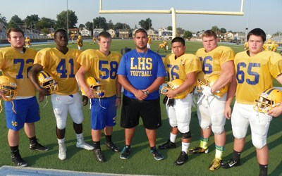 Photo by Jim Hague The Lyndhurst football team looks to be vastly improved this season, thanks to a solid offensive line. From l., are Ryan Smith, Oluwayomi Olasehinde, Michael Fata, head coach Rich Tuero, Joshua Pascual, Matt Schnoll and Michael Cooper.