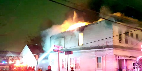 Photo by JeffStang91 on YouTube Firefi ghters train hoses at fl ames raging from 86 Belmont. BOTTOM LEFT: Fire wrecked house an d part of rear garage.