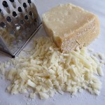 Grated cheese next to cheese grater on counter