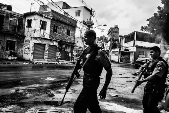 February 2015 - Rio de Janeiro, Brazil: Cops patrolling the streets of Vila Aliança, a favela near Complexo do Alemao. After a militar police cop kill the mototaxi driver Diego da Costa Algavez (22) in the streets of the favela, several cars and high caliber armed cops invaded the streets in alert of a possible confrontation with the gangs and from the population.