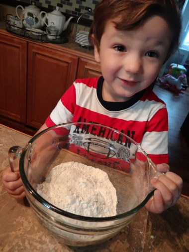 Lucas loves helping. Right now he is in charge of the dry ingredients bowl.