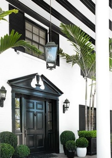 Black front door with boxwoods