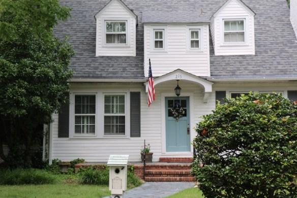 light blue front door with flag