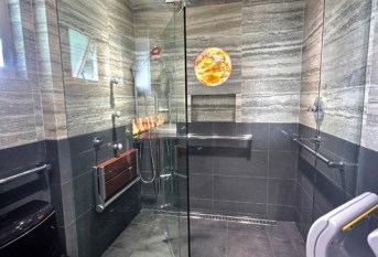 A gorgeous marble tile and gray glass handicap bathroom