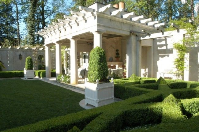 An Exquisite Pergola With Potted Topiaries And Beautiful Hedges. Stunning!