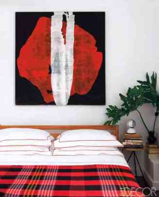Plaid throw in this red and white room cia Elle Decor