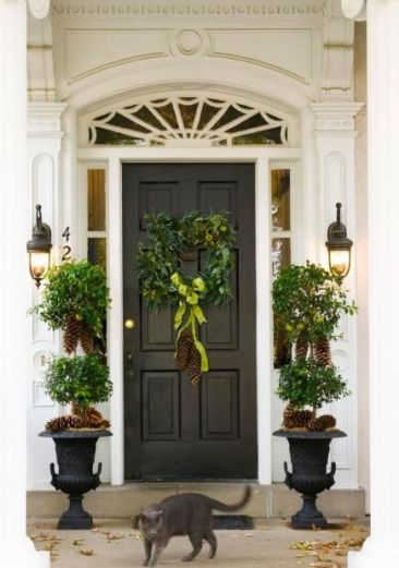Black door entry with pine cone topiaries via Midwest Living