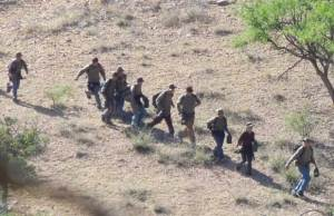Migrants running across the border.