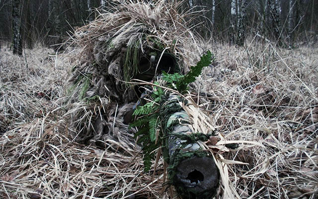 A ghillie suit and the proper application of camouflage can make a sniper almost invisible.