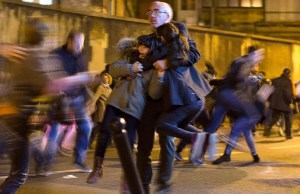 A man carries two children after panic broke out among mourners who payed their respect at the attack sites at restaurant Le Petit Cambodge (Little Cambodia) and the Carillon Hotel in Paris, Sunday, Nov. 15, 2015. Thousands of French troops deployed around Paris on Sunday and tourist sites stood shuttered in one of the most visited cities on Earth while investigators questioned the relatives of a suspected suicide bomber involved in the country's deadliest violence since World War II. (AP Photo/Peter Dejong)