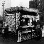 """This New York newsstand from late 1933 displays pulps (including """"The Shadow,"""" """"Blue Book,"""" """"Dime Mystery Magazine,"""" and """"Nick Carter"""") on the wire cage at left, and whole string of pulps (including """"Amazing Stories,"""" """"West,"""" """"Lariat,"""" """"Gang World,"""" """"Cowboy Stories,"""" and """"Doc Savage"""") hanging above the vendors."""