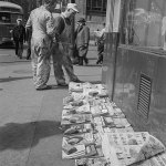 """Among the newspapers and magazines for sale at the corner of E Baltimore and N Holliday streets in Baltimore in March 1943 is an issue of """"Fighting Aces"""" (at the very bottom of the image)."""