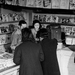 Interned Japanese-Americans shop at the magazine stand in the Tule Lake War Relocation Center in California in March 1944. Several sports pulps from around that time are displayed on a shelf in the background.