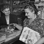 """The caption for this photo, dated Aug. 24, 1945, identifies Genie Pittsley, left, as the clerk at C&S Newsstand in Painesville, Ohio, and Mary Kamenar as a customer. (Kamenar is holding an Aug. 17, 1945, issue of """"The Cleveland Press."""") Just over their shoulders are a number of September and October 1945 pulps, and to their right Penguin paperback books."""