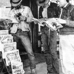 """A trio of cowboys take a break to read through a trio of western pulps: """"Lariat Story Magazine"""" (July 1949); """"Ranch Romances"""" (second issue from May 1949); and """"Texas Rangers"""" (June 1949). The Dallas and Fort Worth newspapers might peg the location as Texas, but there's also a Denver Post for sale."""