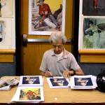 Ernest Chiriacka, one of Pulpcon's guests of honor, signs prints of one of his pin-up paintings, next to a stack of pulp cover prints, at his table in the dealers' room.