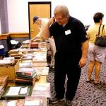 Randy Vanderbeek and others browse the tables displaying items for Saturday night's Pulpcon auction.