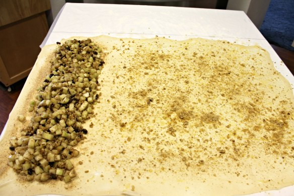 Buttered dough, sprinkled with breadcrumbs & nuts. Apple filling is arranged on bed of breadcrumbs.
