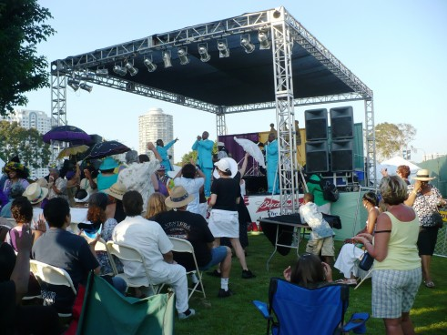 A band in matching turquoise suits and women dancing with colorful umbrellas:  A snapshot of the Long Beach Bayou Festival
