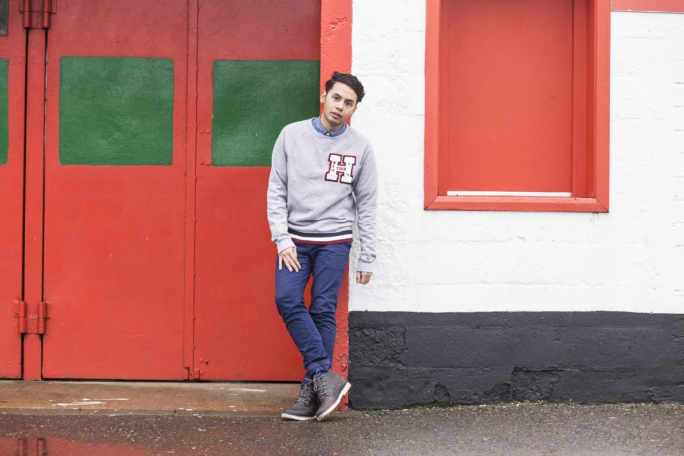 Menswear blogger Ronan Summers styling the 30 anniversary Tommy Hilfiger sweatshirt near a football stadium and jack wills navy trousers